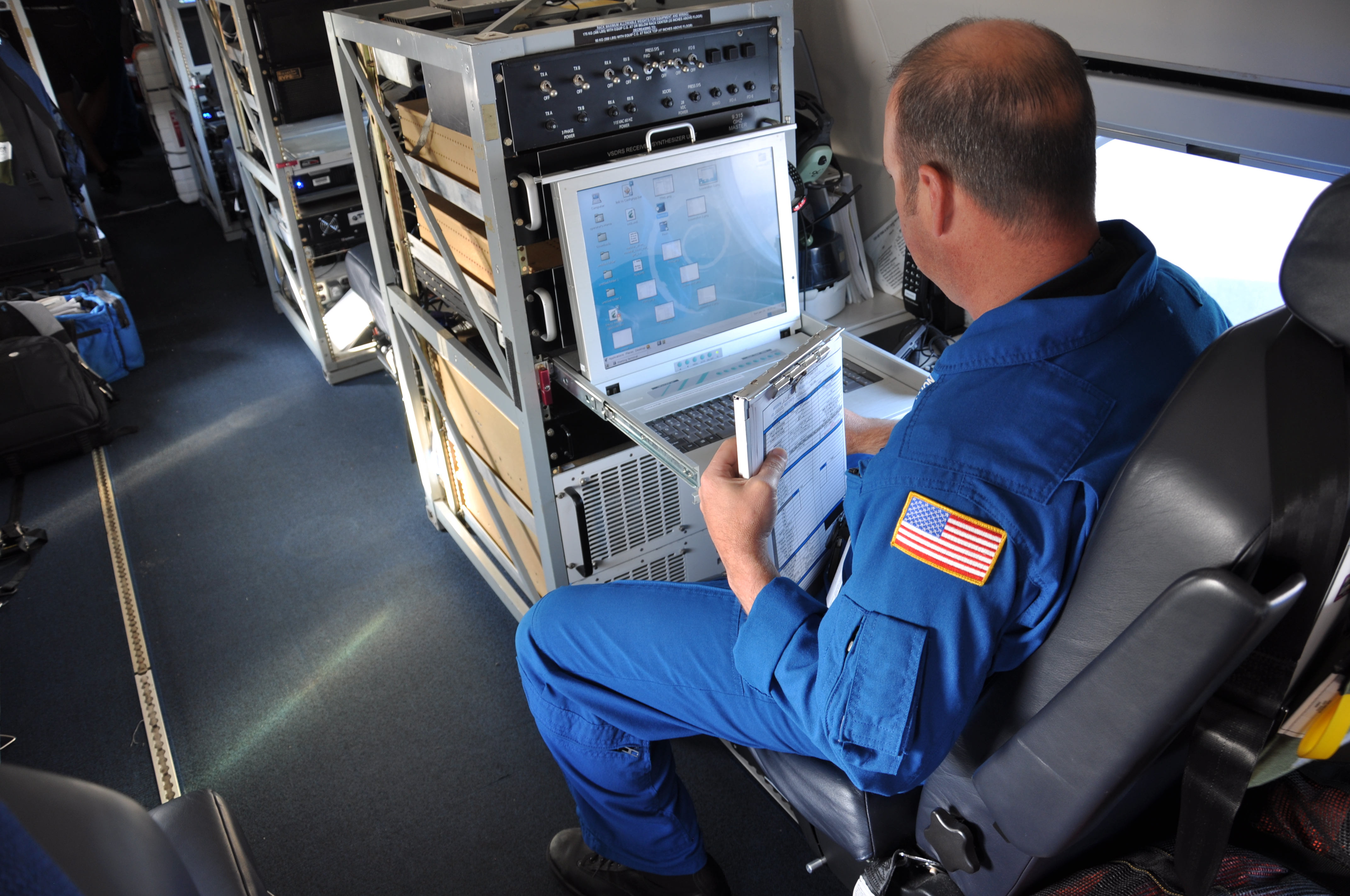 NOAA Aircraft Lead Electronics Technician sits in front of laptop.